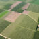Hoeve in landbouwgebied met akkers, graslanden en hagen vanuit de lucht, België Farm in agricultural area with fields, grasslands and hedges from the air, Belgium
